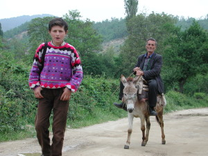 An Albanian in Muhovac man following his son to school on a donkey